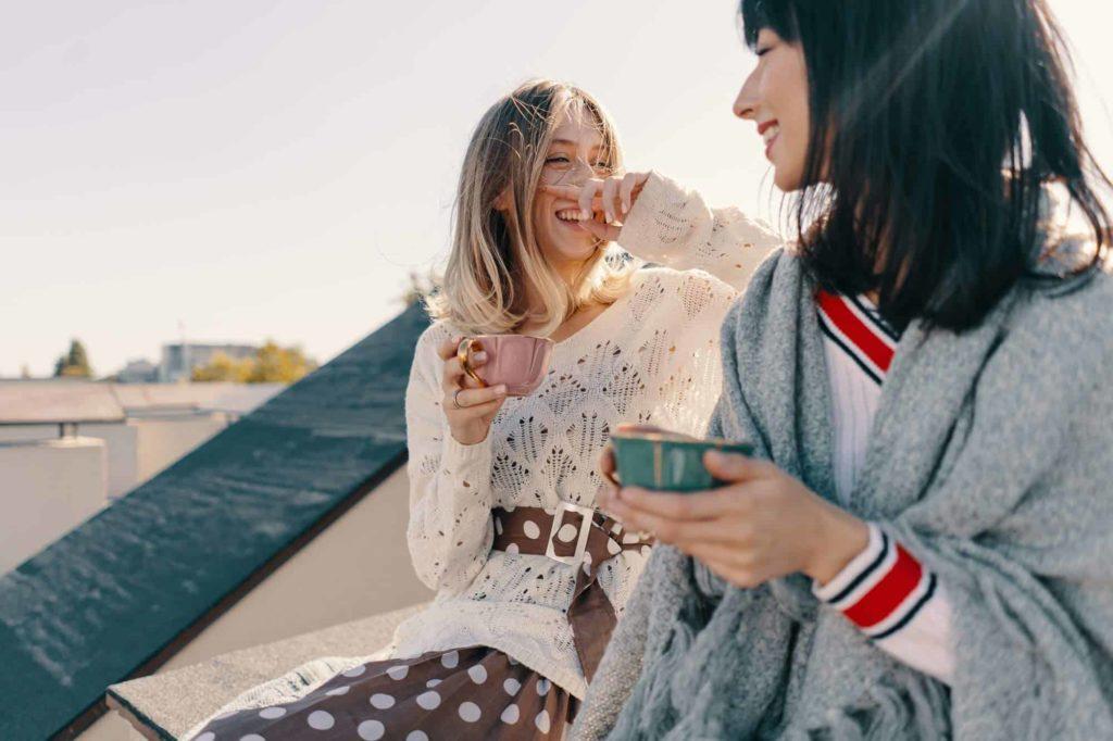 2 fröhliche junge Frauen mit Tassen in der Hand auf dem Dach eines Hauses