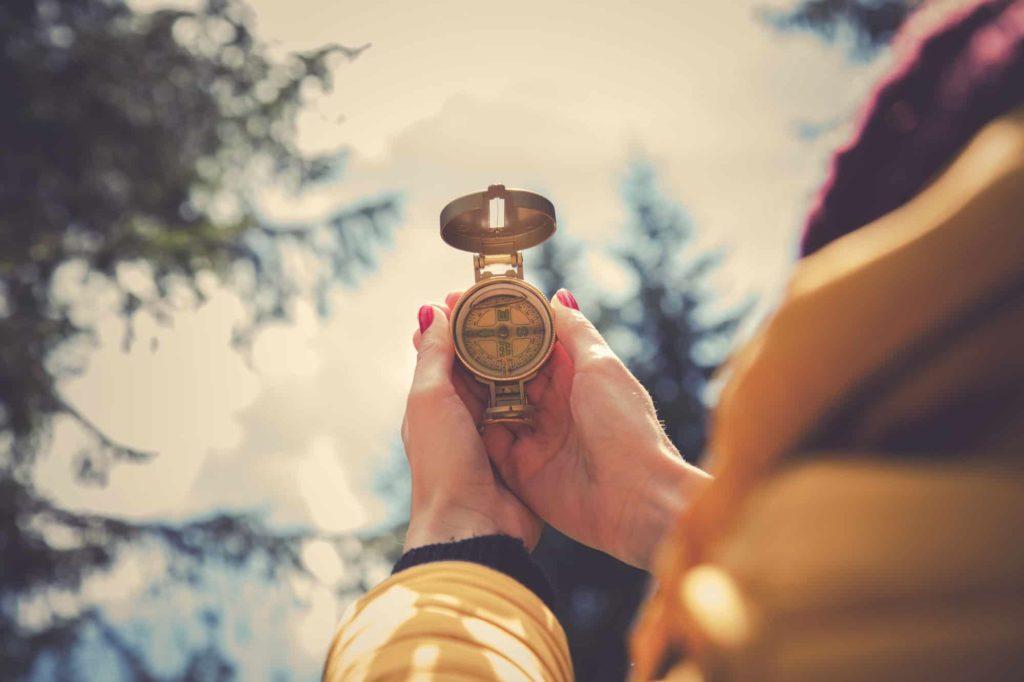 Frau hält einen Kompass in der Hand