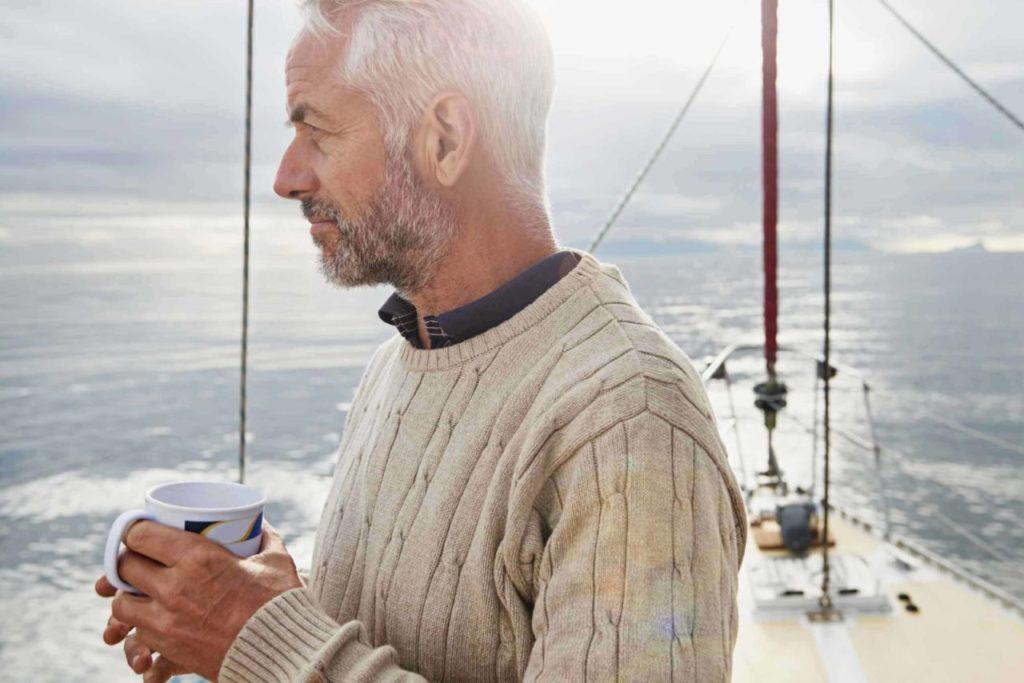 nachdenklicher Mann mit Tasse in der Hand auf einem Segelbot