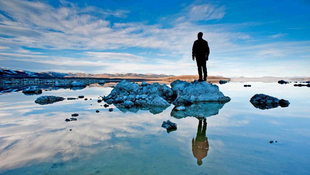 Mann auf Steinen im Wasser