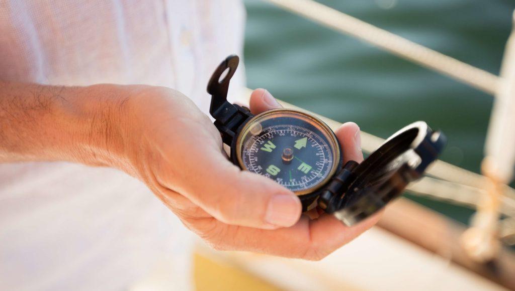 Mann hält einen Kompass in einer Hand