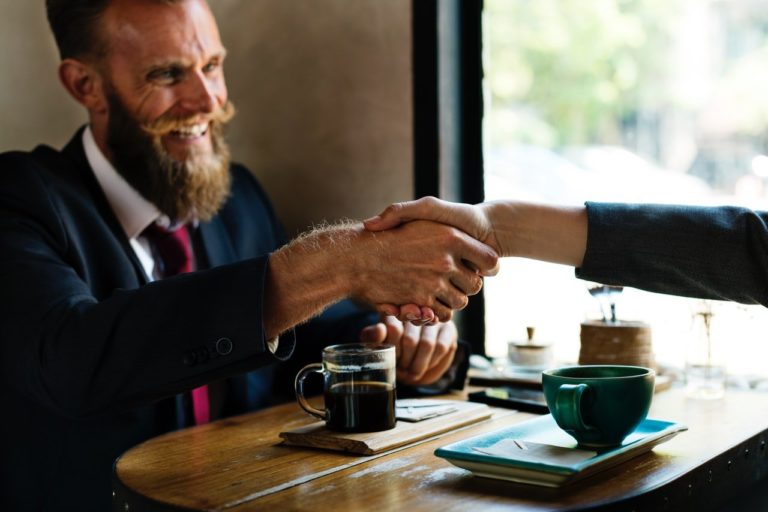Fröhlicher Mann mit Bart schüttelt einer anderen Person die Hand