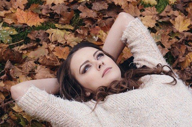 Mädchen liegt auf Herbstlaub