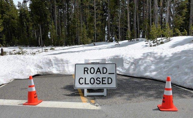 """Schild """"Road closed"""" steht auf einer abgesperrten Straße"""