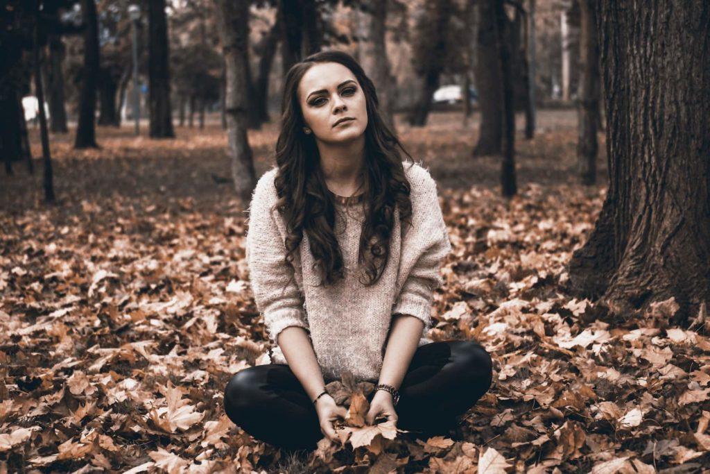 Trauriges Mädchen sitzt in einem Wald